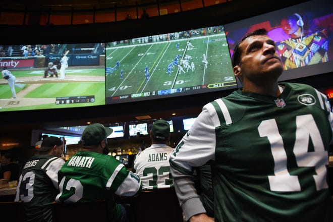 Fans watch the game on large screens including, Pete Scaramelli (R) of Rutherford during a Jets game viewing party for fans at the FanDuel Sportsbook, located at Meadowlands Racing & Entertainment area in East Rutherford on 09/10/18.