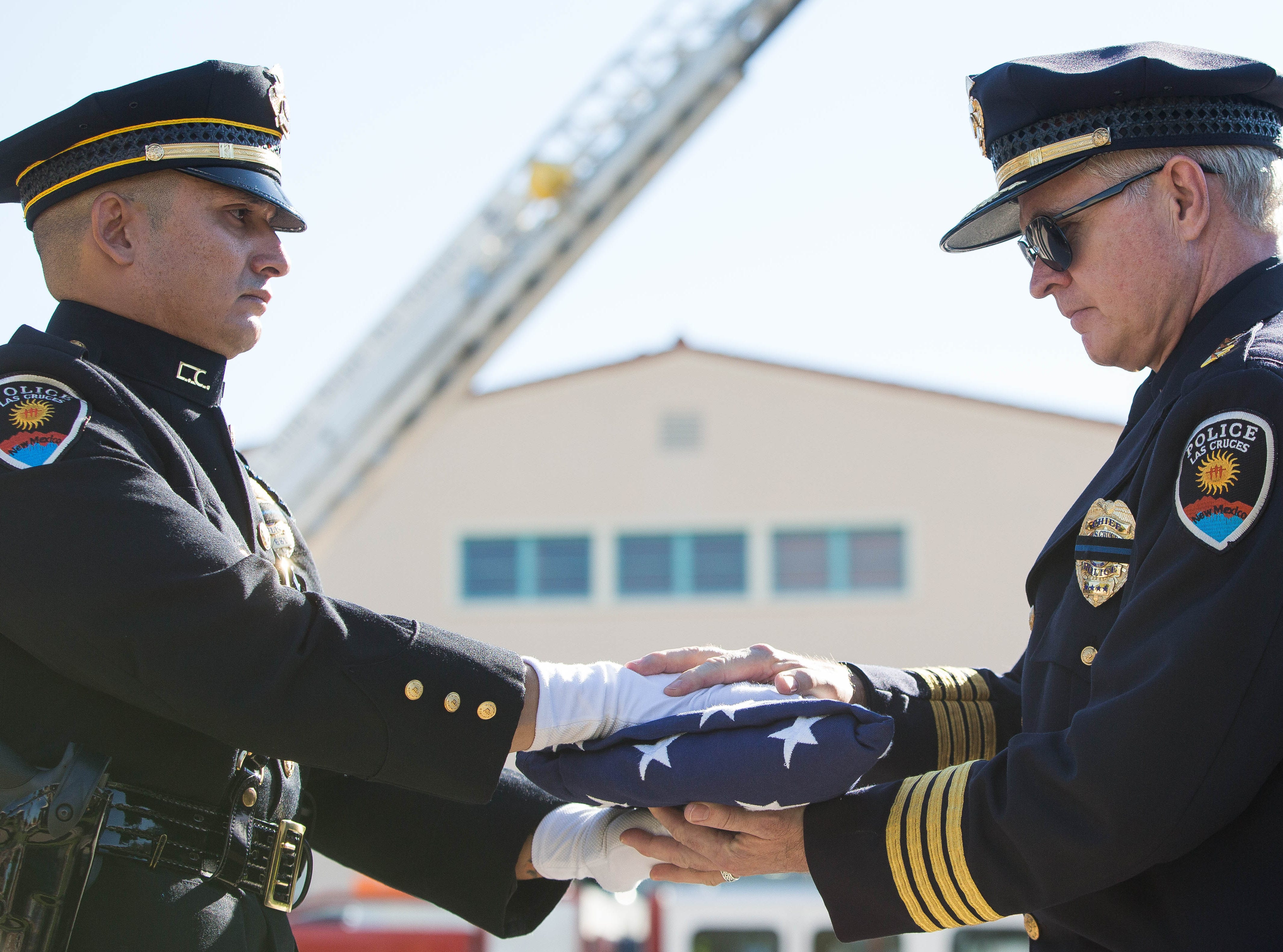 Las Cruces Police Officer Daniel Lopez, left, hands a folded American flag to Police Chief Patrick Gallagher at the closing of the Patriot Day ceremony at New Mexico State University, Tuesday Sept. 11, 2018.