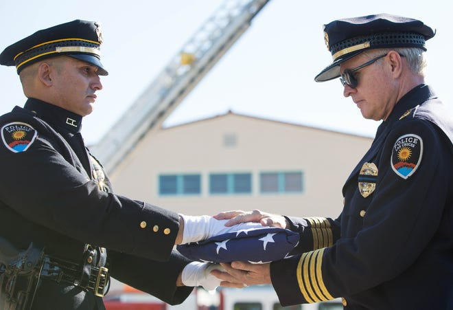 Las Cruces Police Officer Daniel Lopez, left, hands a folded American flag to Police Chief Patrick Gallagher at the closing of the Patriot Day ceremony at New Mexico State University, Tuesday, Sept. 11, 2018.