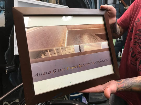 Josh Marchand shows a photo of the National September 11 Memorial in New York City, with a close-up of his father's name.
