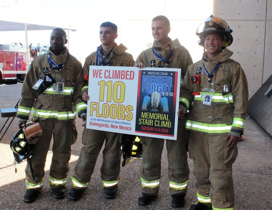 Firefighters Jesse Wilson, Jeffrey Walsh, Owen Ball and Lance Glew hold up a sign signifiying they completed the 9/11 stair climb.