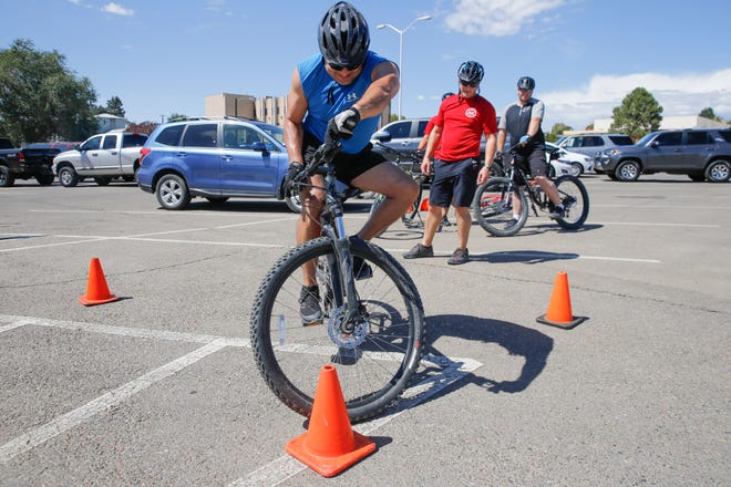 Farmington police Officer Jonathan Covarrubias attempts to hold his bike in a track stand position for 10 seconds Monday during a Law Enforcement Bike Association certification class downtown Farmington. Five Farmington police officers were enrolled in the five-day course to become certified bike officers. Upon completion of the course, the officers will patrol local streets and trail areas such as Berg and Animas parks while riding bicycles.
