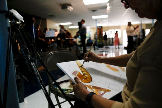 Artist Bev Taylor paints a picture during the Young Audiences concert  Tuesday at Park Avenue Elementary School in Aztec.