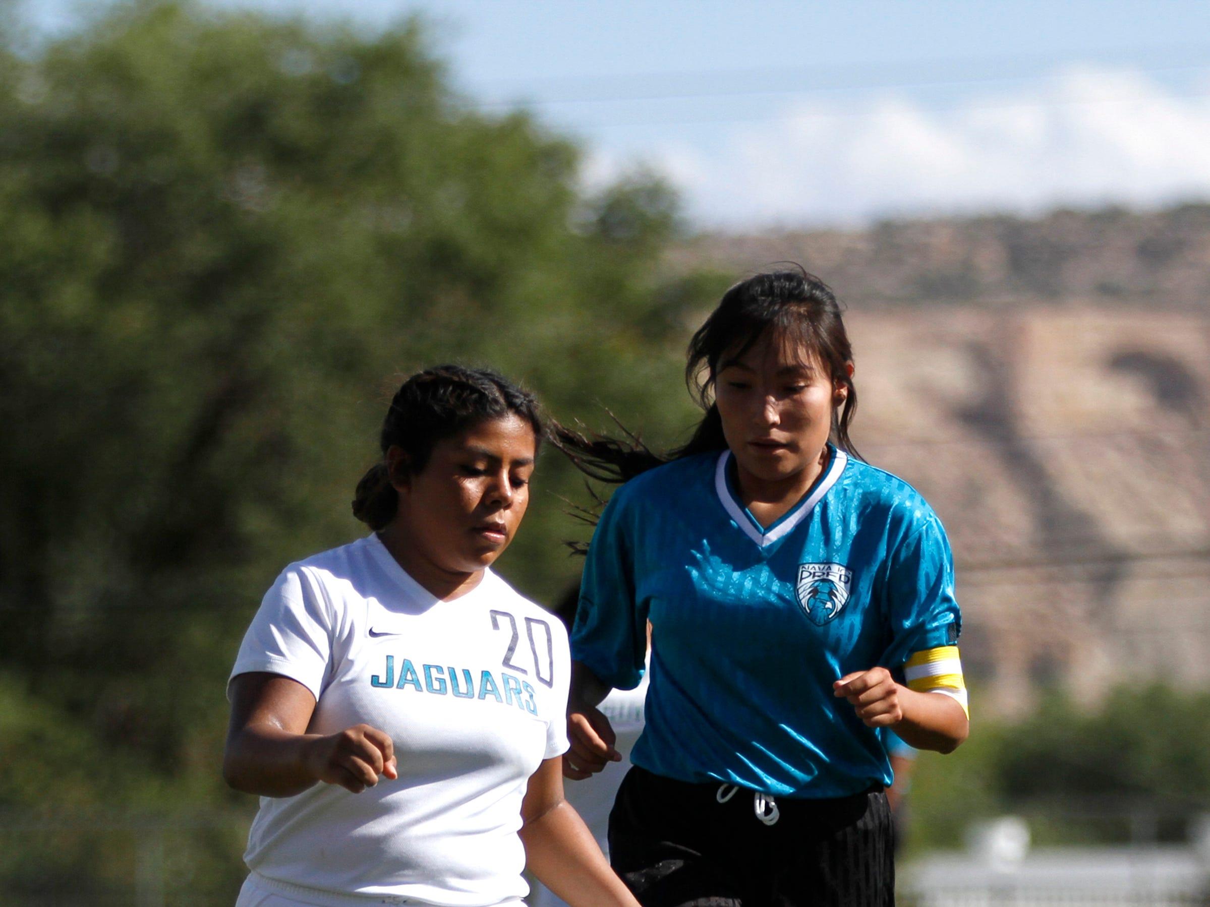 Navajo Prep's Geena Tsosie challenges Capital's Estefani Chali for possession of the ball, Tuesday, Sept. 11, 2018 at Eagle Stadium in Farmington.