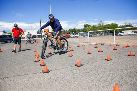 Instructor Greg Erickson, left, a Farmington police officer, gives pointers to Officer Will Nez as he practices navigating his bike through an obstacle course Monday during a Law Enforcement Bike Association certification class in downtown Farmington.