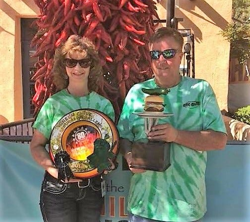 Capitan's Oso Brill owners Pam and Brian Cleckler hold their trophies for winning the Green Chile Cheeseburger Challenge at the New Mexico State Fair Monday.