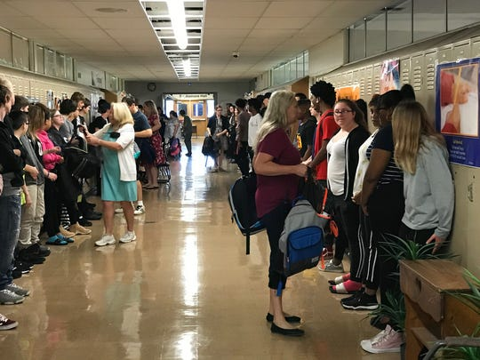 Students line the hallways, waiting to receive backpacks from the Cambridge staff.