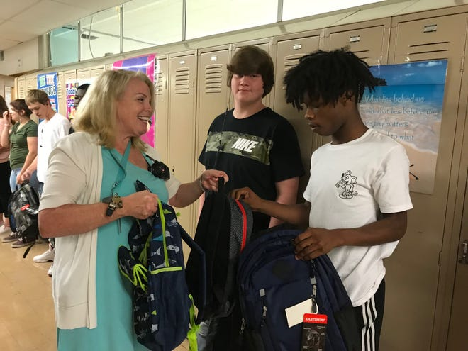 Cambridge High School director Debbie Eves joins her staff in passing out backpacks to students.