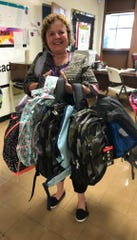 Reading specialist Mar Ann Brewer is ready to pass out backpacks to Cambridge students in the 9-10 Hall.