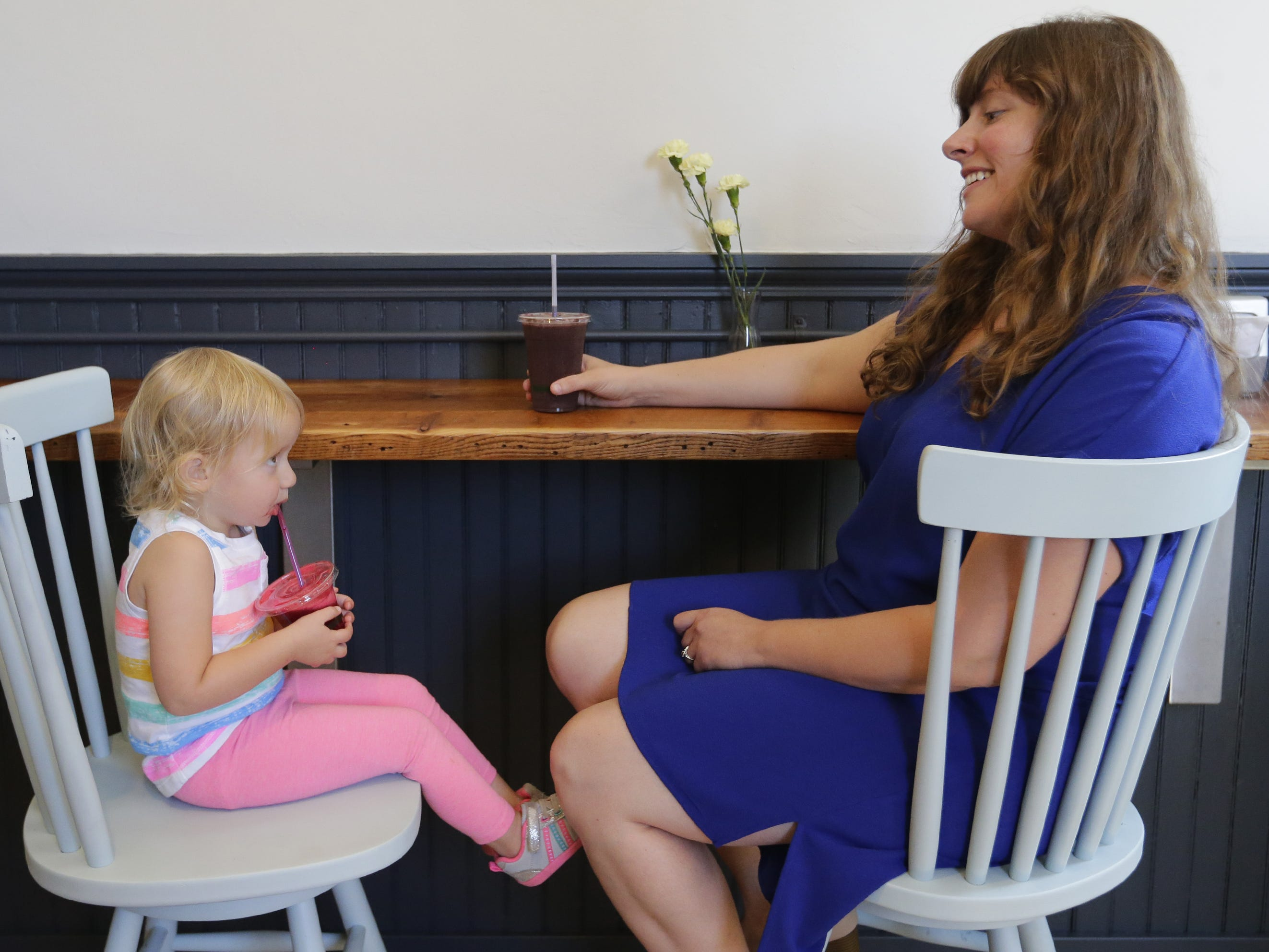 Megan Bartelt has a juice drink with her 2-year-old daughter, Iris Thede, on Tuesday, Sept. 11, 2018, at Carrot & Kale in Oshkosh. Bartelt opened the organic juice bar and cafe this summer at 110 Algoma Blvd.