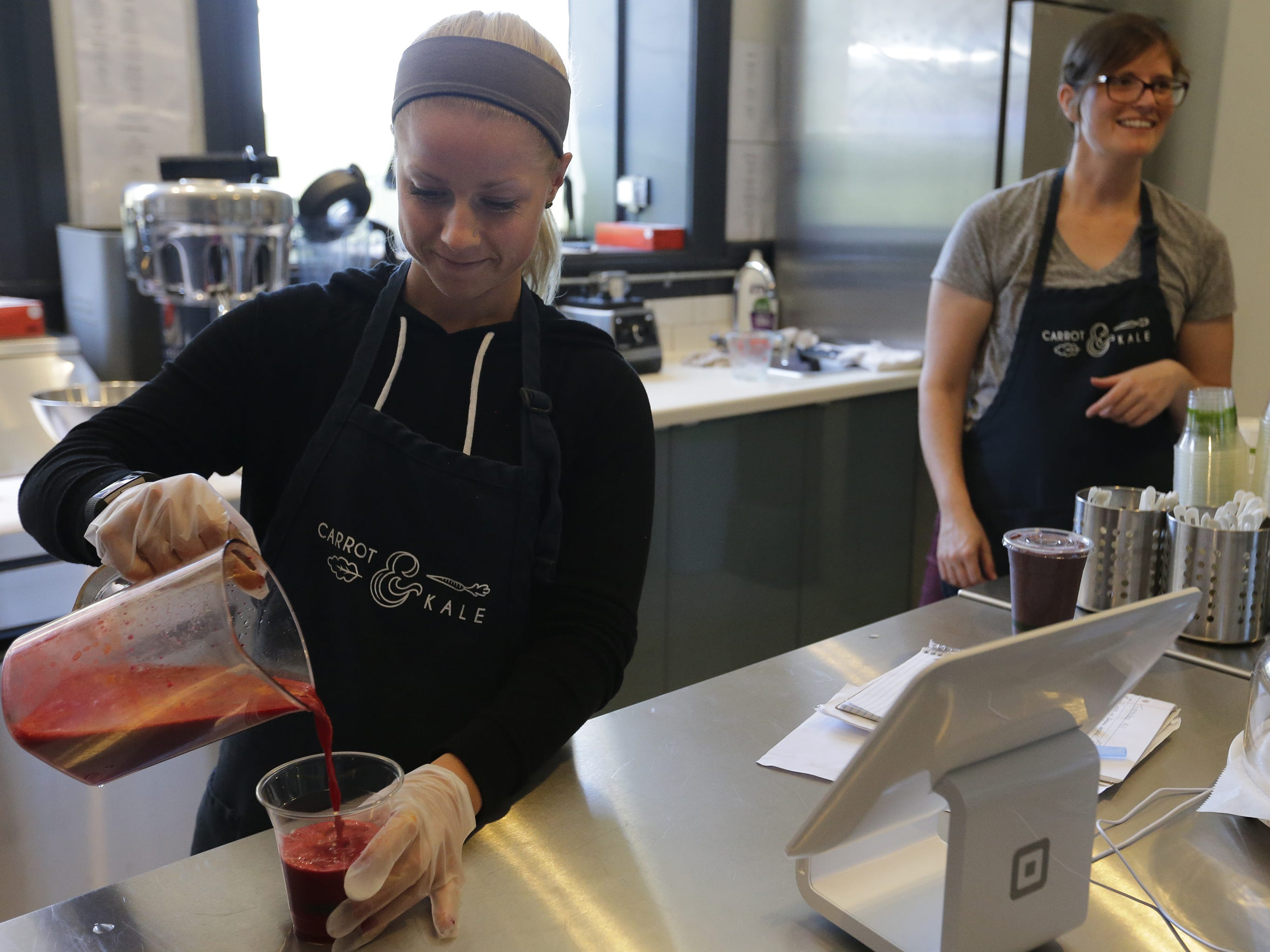 Courtney Holland, left, pours a beet juice drink as Lauren Bartelt talks with a customer Tuesday, Sept. 11, 2018, at Carrot & Kale in Oshkosh. The organic juice bar and cafe, 110 Algoma Blvd., offers healthy food and drink options in the city.