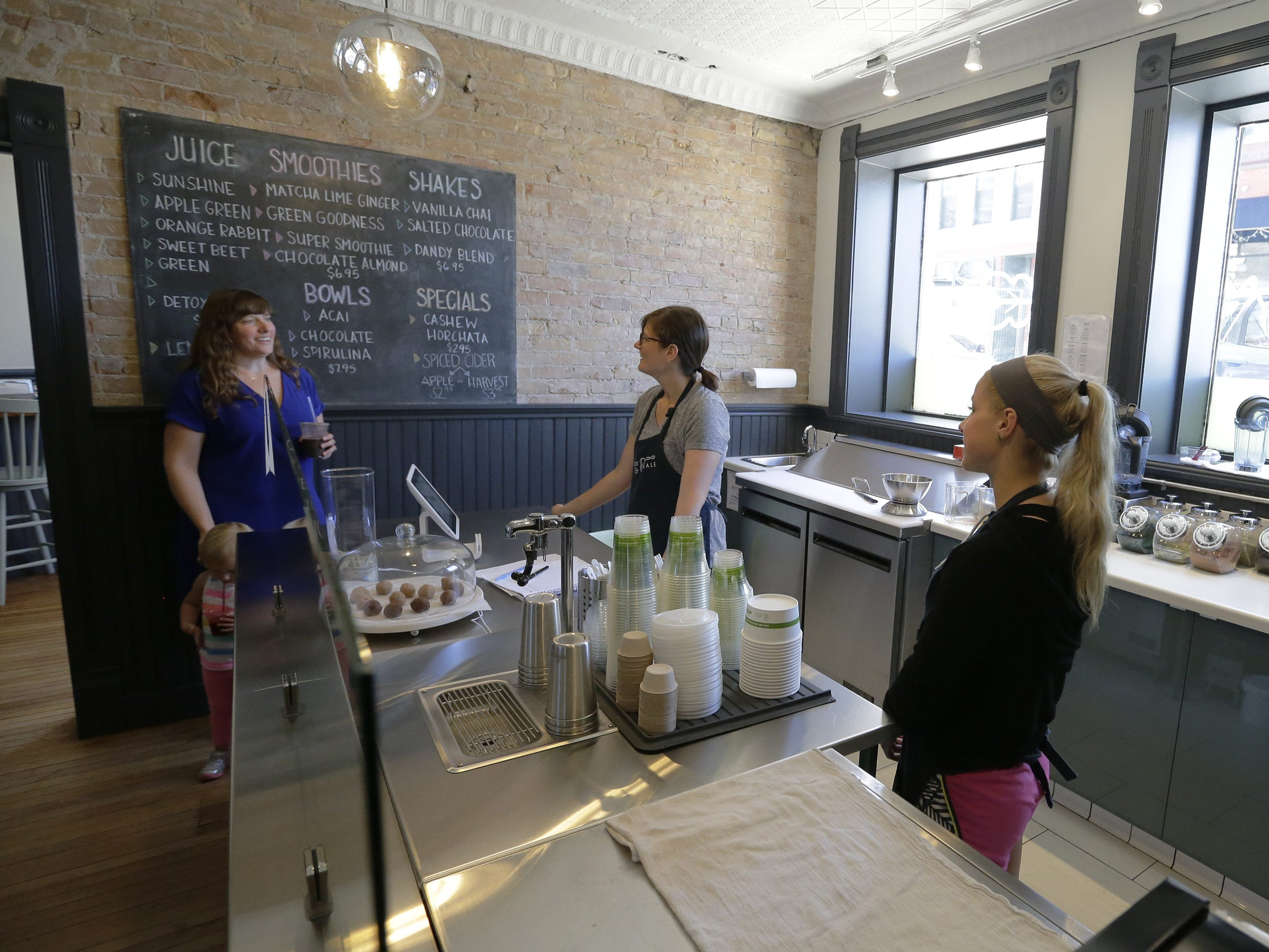 Carrot & Kale owner Megan Bartelt, from left, talks with Lauren Bartelt and Courtney Holland on Tuesday, Sept. 11, 2018, inside the organic juice bar and cafe, 110 Algoma Boulvard in Oshkosh.