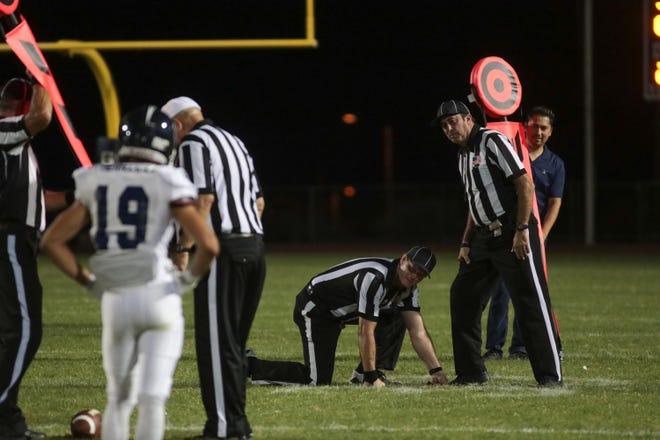 Referees measure for a first down at a Desert Hot Springs football game against Jurupa Valley, Desert Hot Springs, Calif., September 6, 2018.