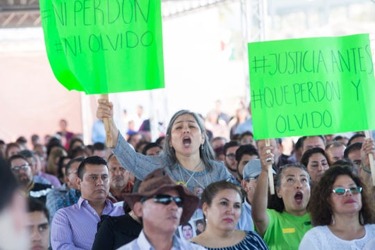 "Women hold signs reading ""No Pardon, No Forgetting"" during the sixth public forum on ""Pacification and National Reconciliation"" at the Uiniversidad Iberoamericana in Tijuana on September 11, 2018."