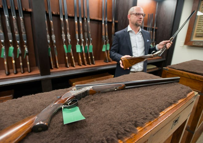 """Director E. Duke """"L.D.""""McCaa II talks about the Holland & Holland shotgun that he is holding versus the Westley Richards shotgun, in the foreground, for sale at the Westley Richards Agency U.S.A. in Gulf Breeze on Tuesday, September 11, 2018."""