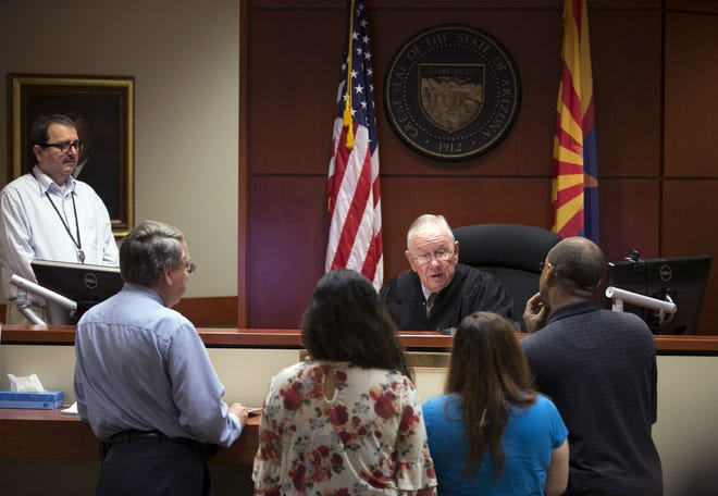 Judge Pro Tempore Reid Southern speaks with tenants as Kevin Holliday (second from left) an attorney for the landlord and court clerk Carlos Arce (left) look on during eviction court at the Maricopa County court building, in Surprise on Thursday August 16, 2018.
