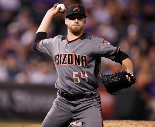 Arizona Diamondbacks relief pitcher Jimmie Sherfy throws to first base to put out Colorado Rockies' David Dahl in the eighth inning of a baseball game Monday, Sept. 10, 2018, in Denver. The Rockies won 13-2.