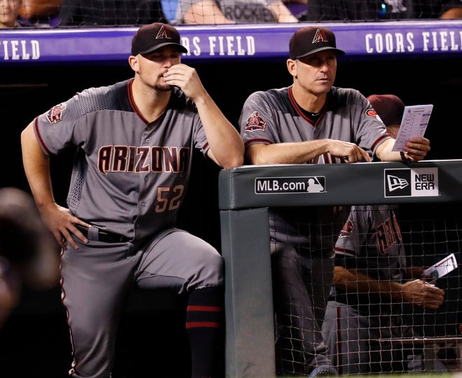 Arizona Diamondbacks starting pitcher Zach Godley, left, looks on with manager Torey Lovullo from the dugout as the Diamondbacks bat against the Colorado Rockies in the sixth inning of a baseball game Monday, Sept. 10, 2018, in Denver.