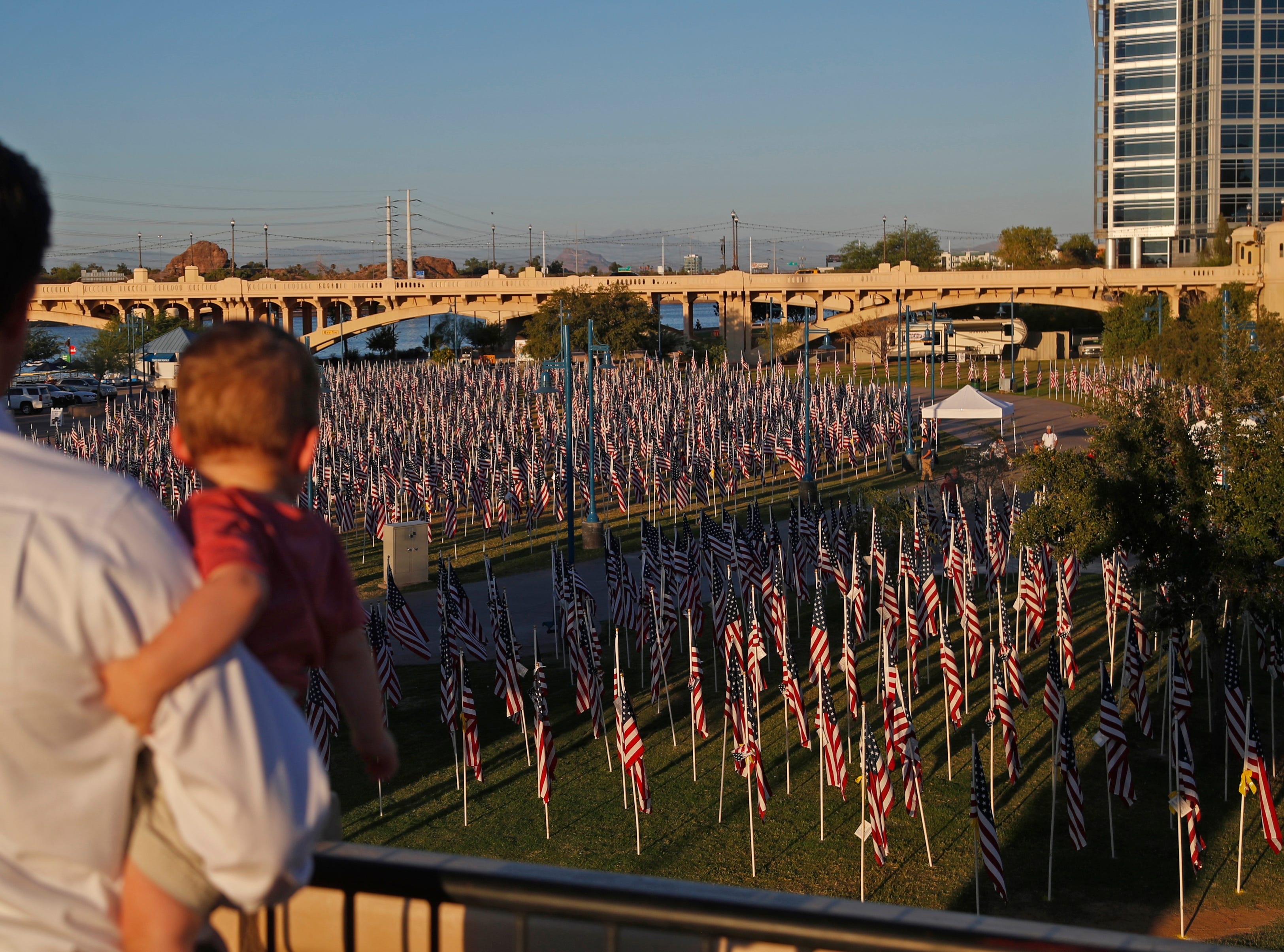 Marcus Johnson holds his son William Johnson, 1, as they look over the flags at the Healing Field at Tempe Beach Park in Tempe on Sept. 10, 2018.