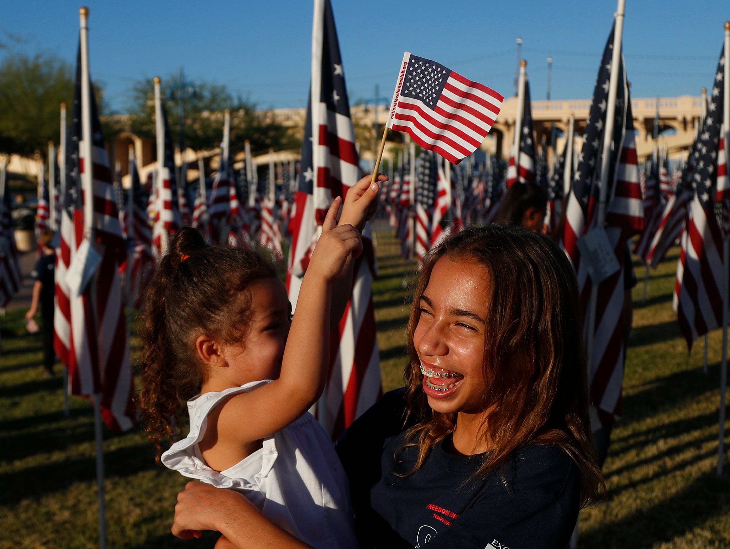 Destiny Blackford, 13, laughs as she holds Bella Calderon, 3, waving a flag at the Healing Field at Tempe Beach Park in Tempe on Sept. 10, 2018.