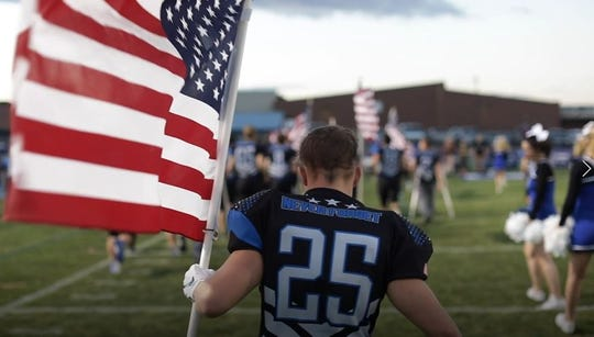 Snowflake senior linebacker/running back David Brimhall carries the American flag onto the field before a Sept. 7 home game against Page.