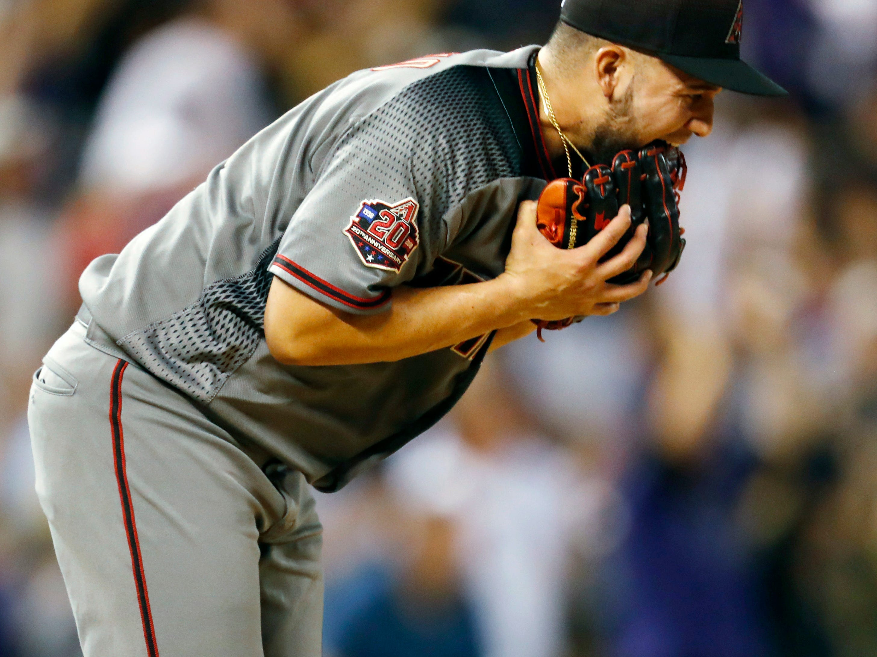 Arizona Diamondbacks relief pitcher Silvino Bracho bites his glove after giving up a three-run home run to Colorado Rockies' Trevor Story in the fifth inning of a baseball game Monday, Sept. 10, 2018, in Denver.