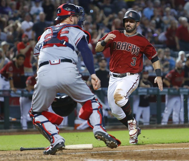 Diamondbacks' Daniel Descalso (3) comes home against Braves catcher Tyler Flowers (25), scoring during the sixth inning at Chase Field in Phoenix, Ariz. on Sept. 9, 2018.