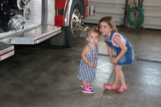 Vada Miller, 6, checks out fire trucks with her little sister, Stella, who at 19-months-old is dealing with cystinosis, a rare genetic disease.