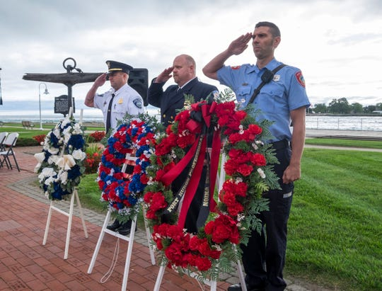 Port Huron Police Sgt. Jason Barna, left, salutes with Tri-Hospital EMS Paramedic Supervisor Bill Adams, center, and Port Huron Firefighter Matt Oleaga while presenting wreaths Tuesday, Sept. 11, 2018, during a 9/11 memorial service at the International Flag Plaza in Port Huron.