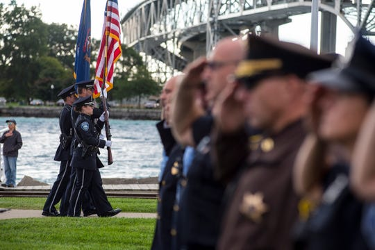 Officers from the Port Huron Police Department carry the flags past first responders holding a salute Tuesday, Sept. 11, 2018, during a memorial service at the International Flag Plaza in Port Huron.