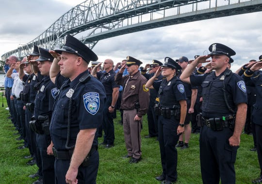 Members from local first responding agencies hold a salute as the colors are presented Tuesday, Sept. 11, 2018, during a memorial service at the International Flag Plaza in Port Huron.