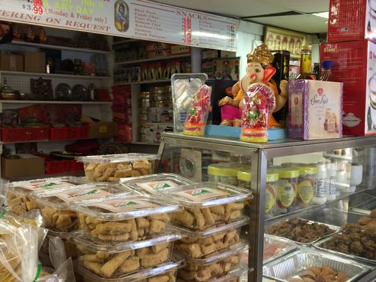 The counter at Krishna Indian Grocery in Poughkeepsie shows a variety of products and food.
