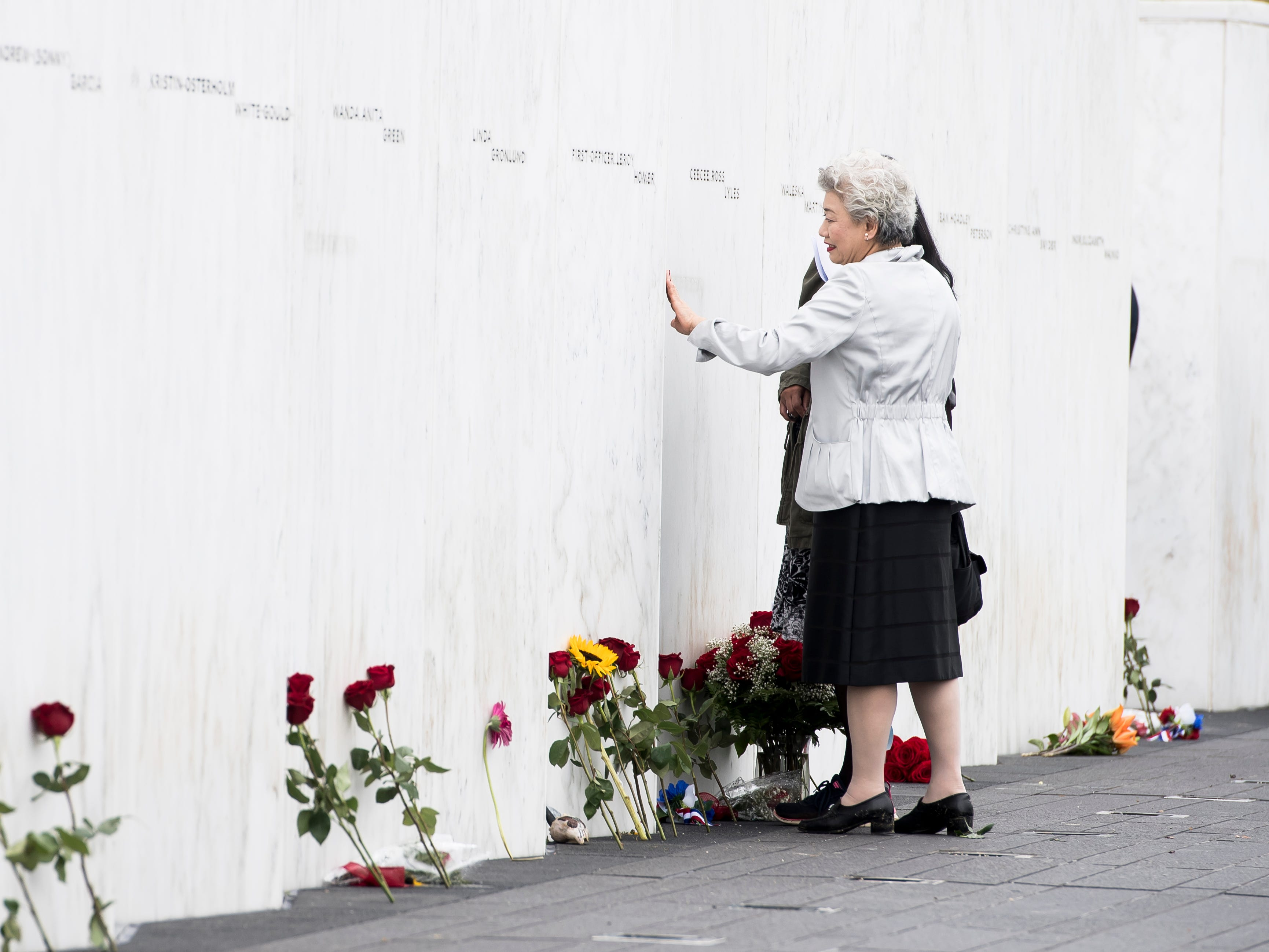 Yachiyo Kuge, mother of Flight 93 victim Toshiya Kuge, touches his name on the Wall of Names at the Flight 93 National Memorial in Shanksville, Pa., on September 11, 2018.