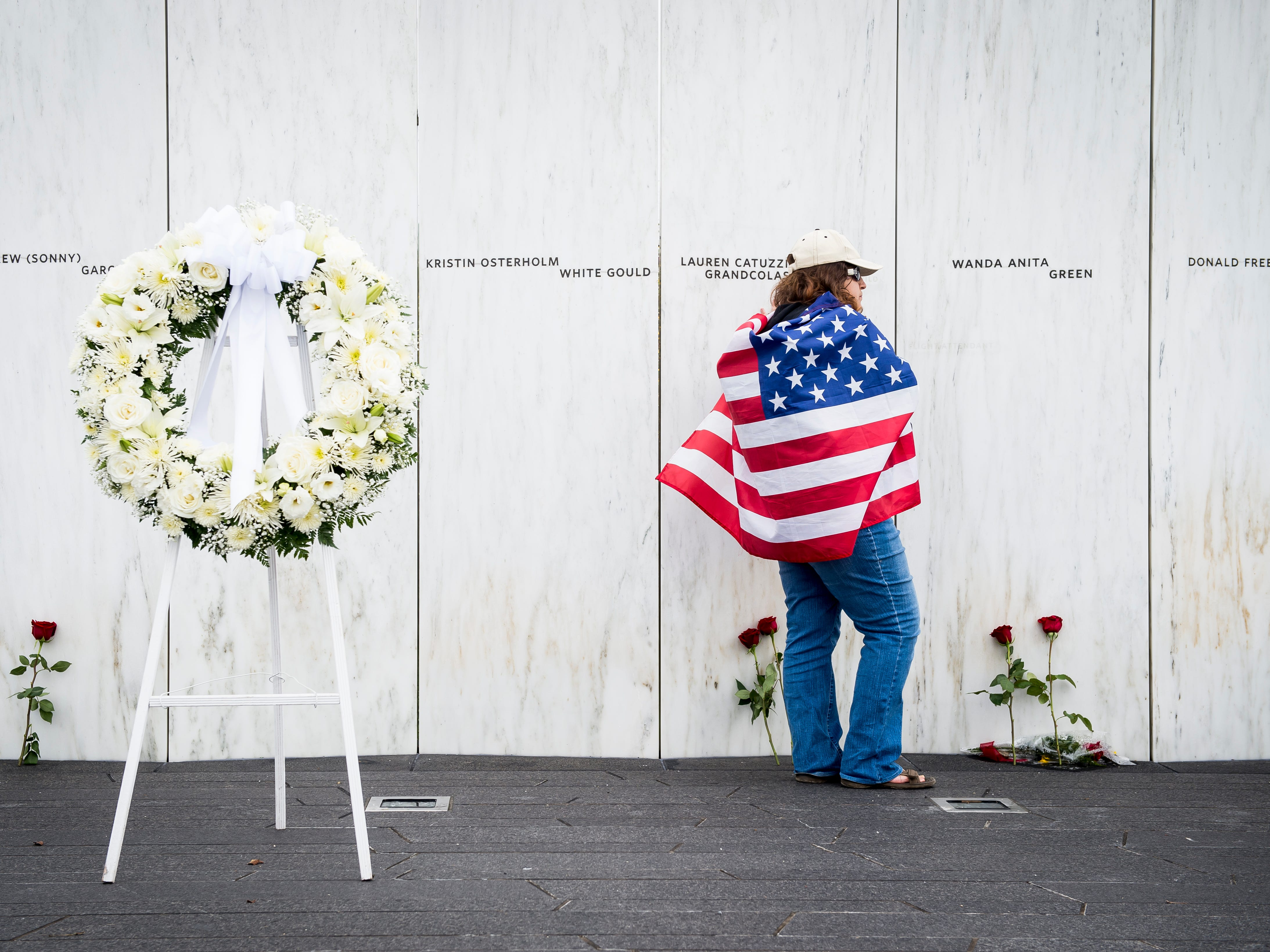 Standing at the Wall of Names Memorial, Chrissy Bortz, of Latrobe, Pa., stops and touches each of the 40 names of the victims who were killed in the Flight 93 crash in Shanksville, Pa., Tuesday, September 11, 2018.
