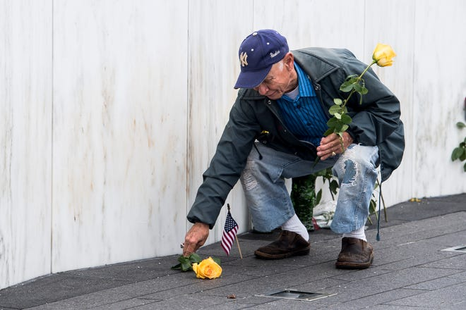 Larry Gray Fair, of Boonsboro, Maryland, places flowers at the Wall of Names at the Flight 93 National Memorial September 11, 2018.