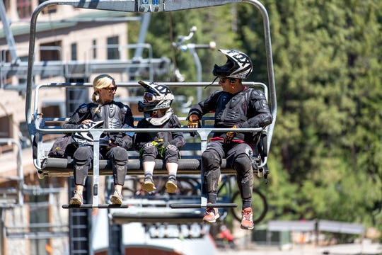 A family rides the lift to Northstar's bike park.