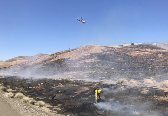 A helicopter drops water on the ridge line above Interstate 80 near Derby Dam east of Sparks on Tuesday, Sept. 11, 2018. Flames came right up to the westbound lanes.
