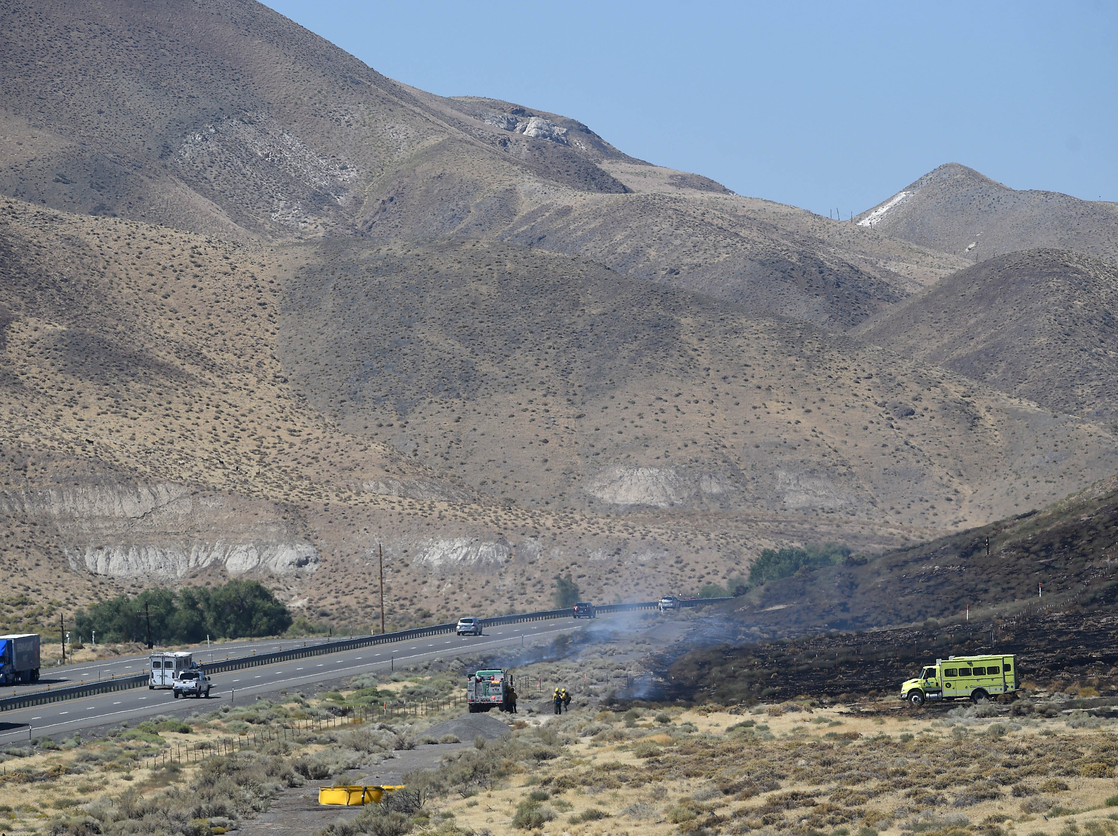 Crews work to contain a small brush fire along the north side of I-80 next to Derby Dam on Sept. 11, 2018.