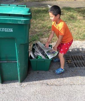 Henry Karpien makes sure neighbor Joann Dale's recycling is in order.