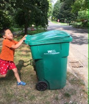 Henry Karpien takes neighbor Joann Dale's garbage toter to the curb in Brighton.