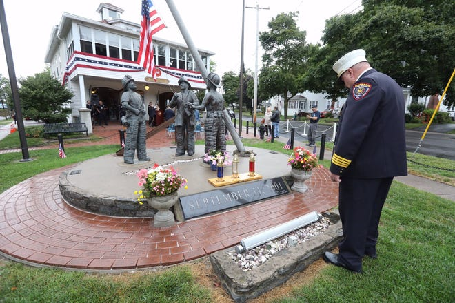 Assistant Chief Steve Dorgan looks at the 9/11 memorial before the start of the vigil with the Brockport Volunteer Firefighters Association.
