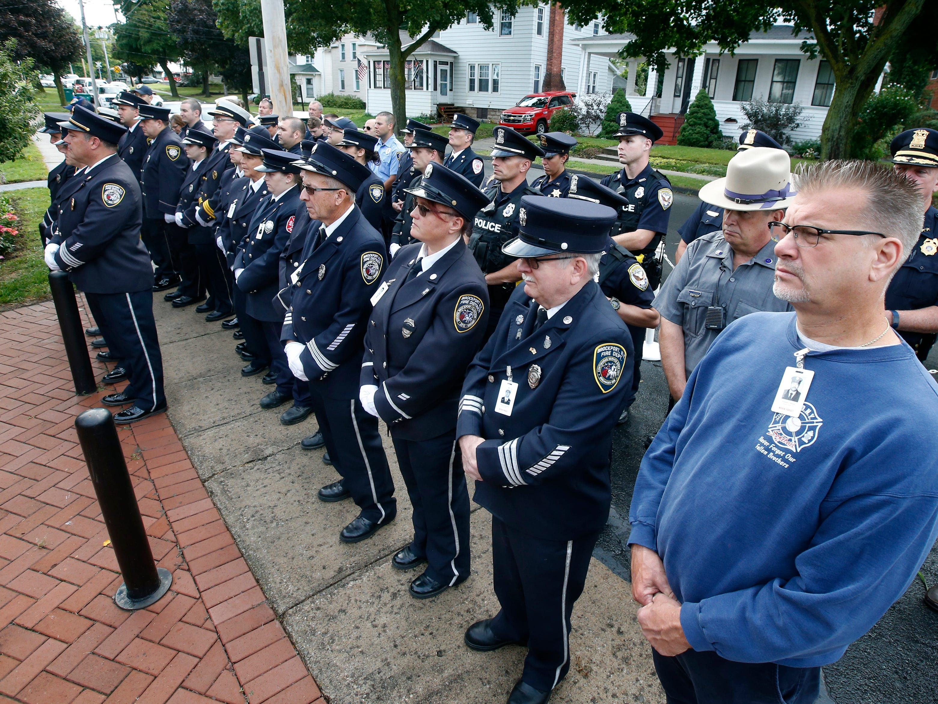 Firefighters and members of law enforcement stand in formation to pay their respects during the September 11th remembrance service at the Brockport Fire Department, Station 4.