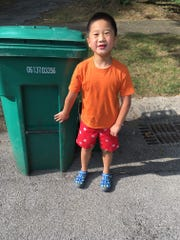 Henry Karpien takes neighbor Joann Dale's garbage toter to the curb in Brighton when she doesn't.