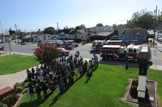 Staff and students from Washington Middle School stand in honor of Tuesday's 9/11 memorial service.