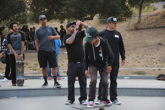 Louis Gutierrez, pictured right, at the Aug. 7 skate park event. In two separate videos posted to the social media platform Snapchat, Gutierrez, then a MILPA community liaison and program assistant, appears to verbally and physically intimidate a child shortly before the child was beaten by another man. Gutierrez was later criminally charged in the incident.