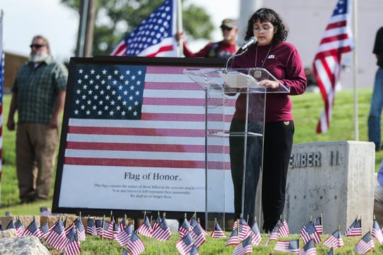 Mira Velez reads a letter by her father, Rosendo Velez, who was a first responder during the 9/11 attack, during the 9/11 Memorial Ceremony Tuesday, Sept. 11, 2018, at the monument near Celebration Bridge.