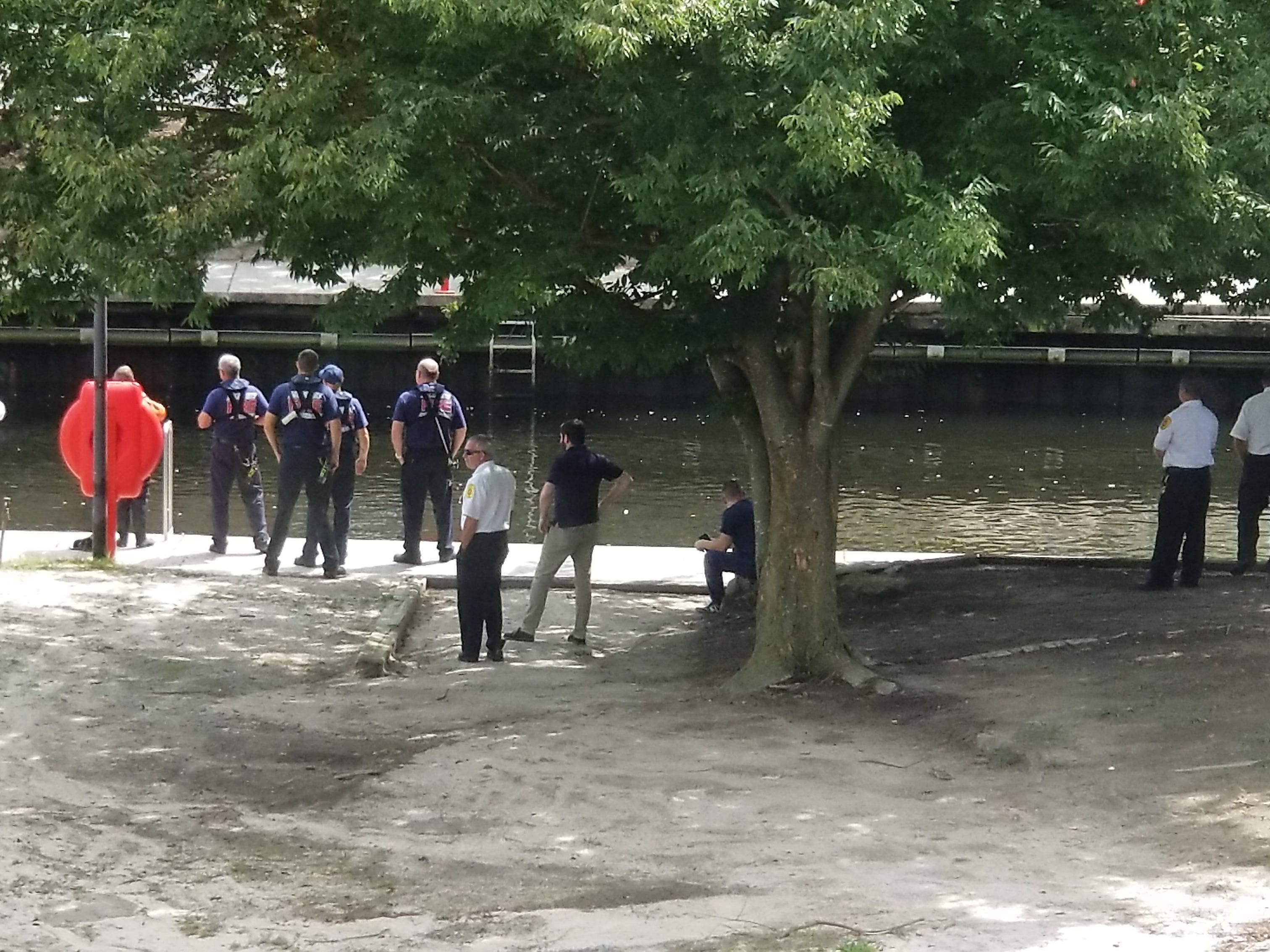 Salisbury police and firefighters watch divers search for a body in the Wicomico River at the South Division Street bridge in Salisbury.