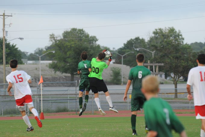 JMB keeper Gabe Dunn goes up for a save during Bennett's boys soccer game against Parkside Monday night at County Stadium.