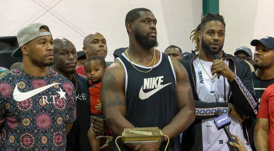 """From left, New Orleans Saints Craig Robertson, Chris Banjo (holding his son, Terron Armstead and Cam Jordan attend the """"Unity in Community"""" rally at Susan Park Playground which was organized as a """"peaceful protest"""" after widely-circulated memo by Kenner Mayor Ben Zahn banning Kenner's recreation booster clubs from purchasing Nike gear, Kenner, La. Monday, Sept. 10, 2018. (David Grunfeld /The Times-Picayune via AP)"""