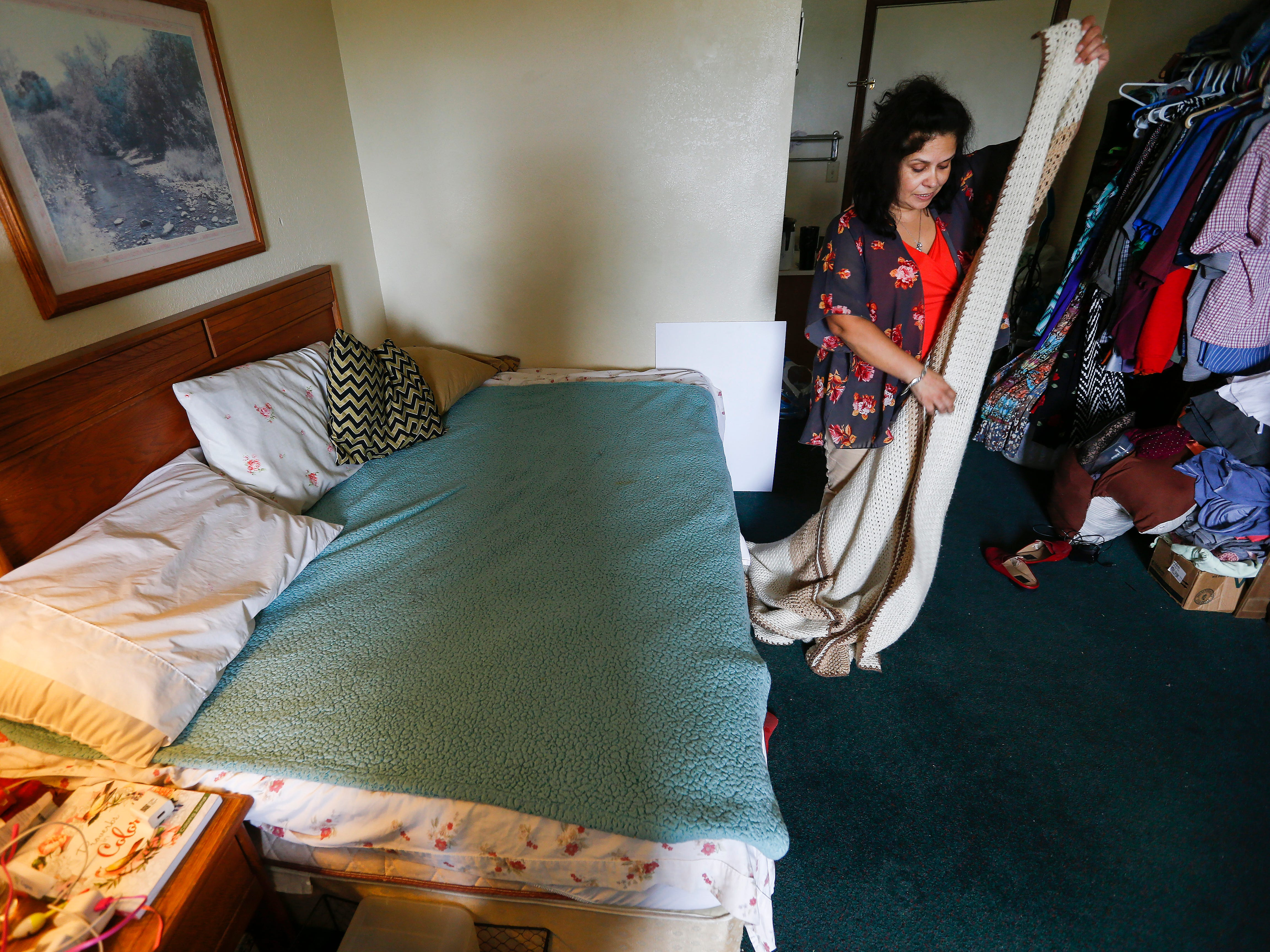 Chrystal Ketterman fixes the bed inside of her room at the extended stay hotel she is living in in Branson on Monday, July 30, 2018.